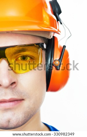 Close-up face portrait of young builder worker in protective hardhat with ear muff and protective glasses - stock photo