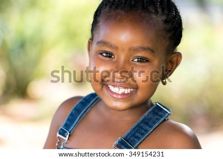 Close up face shot of cute Smiling african girl outdoors. - stock photo