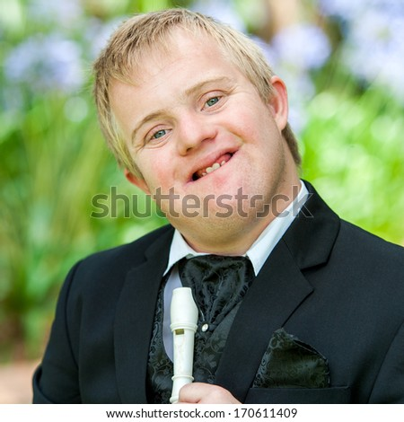 Close up face shot of disabled musician with block flute outdoors. - stock photo
