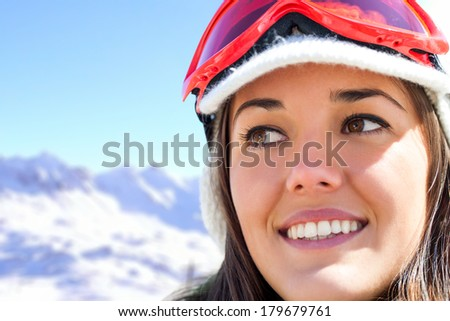 Close up face shot of girl wearing ski goggles in mountains. - stock photo