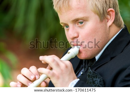 Close up face shot of handicapped boy playing block flute outdoors. - stock photo