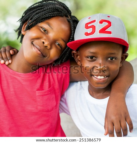 Close up face shot of smiling African boy and girl outdoors. - stock photo