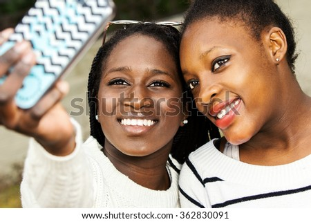 Close up face shot of two afro american teen girls taking self portrait with smart phone.