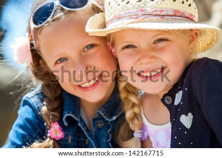 Close up face shot of two young girlfriends smiling with heads together outdoors. - stock photo