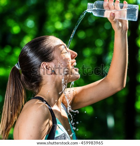 Close up face shot of young fitness girl  pouring cold water on face after jog.Woman in forest against green background.
