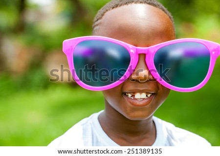 Close up face shot portrait of cute African boy wearing huge over sized sun glasses outdoors. - stock photo