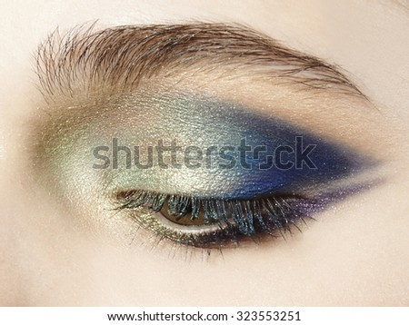 close up face with blue gold green eyeshadow make up - stock photo