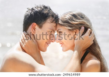 Close-up faces of couple in love against sunlight background - stock photo