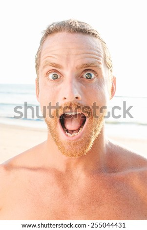 Close up Facial Expression of a Shocked Bare Handsome Man with Wide Open Eyes and Open Mouth. Captured at the Beach. - stock photo