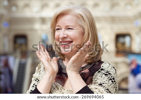 Close up facial portrait of a beautiful senior woman friendly smile and attentive expression - stock photo