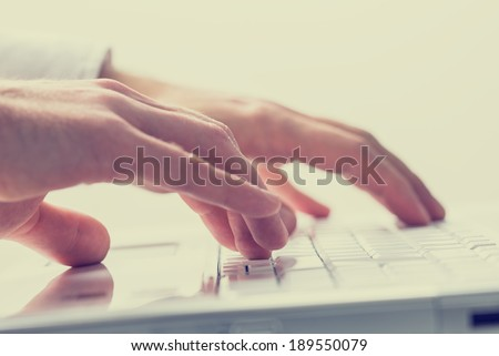 Close up faded effect retro style image of the hands of a man typing on a laptop keyboard. - stock photo