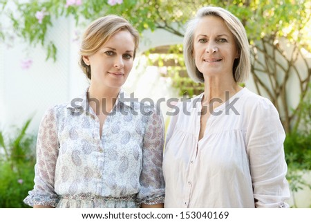 Close up family portrait of an adult daughter with her mature mother standing next to each other while relaxing in a home garden together, outdoors.