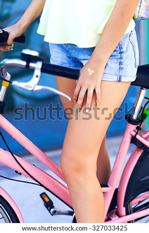 Close up fashion details of stylish woman riding vintage pink bike, bright colors, summer vacation, wearing denim mini shorts , trendy manicure nails and accessorizes .