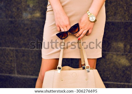 Close up fashion details, young business woman holding bag and retro sunglasses, golden jewelry, warm colors. - stock photo