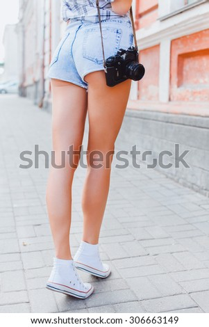 Close up fashion image of gorgeous woman with perfect body and butt holding retro vintage camera,hight heels,photographer girl,trip,old city,going crazy,summer warm colors,toned - stock photo