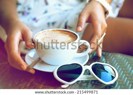 Close up fashion image of woman holding  white cup of her morning cappuccino, wearing white stylish dress, and put her vintage heart sunglasses to the table, enjoy her time alone. Instagram colors. - stock photo