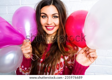 Close up fashion lifestyle image of young brunette woman with bright make up and amazing smile holding pink path balloons. - stock photo