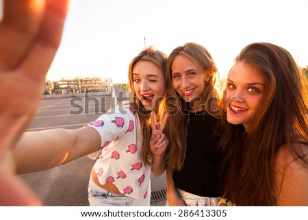 Close up fashion lifestyle portrait of tree young hipster girls best friends, wearing bright make up and similar trendy outfit,making funny faces and have gait time.Urban background.girls make selfie - stock photo