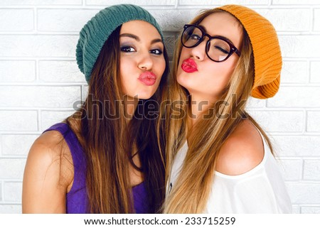 Close up fashion lifestyle portrait of two young hipster girls best friends, wearing bright make up and similar trendy hats, making funny faces and sending kiss. Urban white brick wall background. - stock photo