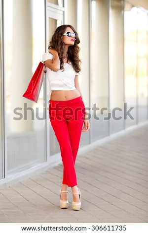 Close up fashion lifestyle portrait young hipster girl, with shopping bags walking out from shop - stock photo