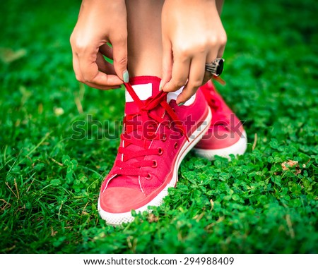 Close up fashion photo of bright pink female sneakers and hands tying shoelaces .  Fashion image of woman legs , wearing stylish keds and big diamond ring, staying on the grass, bright colors.