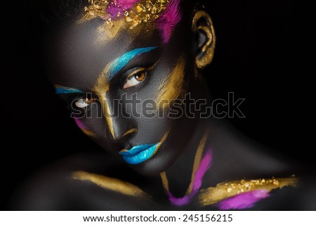 close-up fashion portrait of a dark-skinned girl with color make-up - stock photo