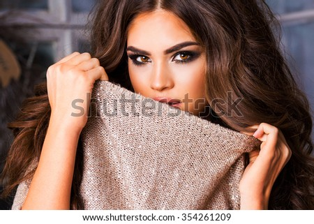 Close up fashion portrait of amazing  elegant  charming woman with bright  make up in warm  sweater over  light christmas background. - stock photo