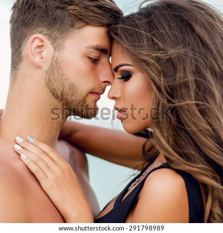Close up  fashion portrait of beautiful sensual woman and her handsome boyfriend with perfect tan body posing on the beach. Couple in love hugging . Summer evening warm mood.