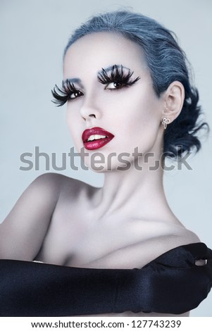 Close-up fashion portrait of beautiful woman face with creative art make up and eyelashes - stock photo