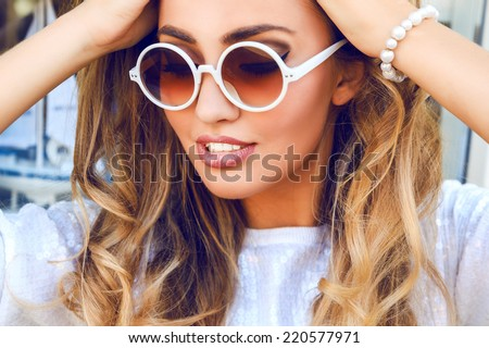 Close up fashion portrait of beautiful woman with perfect skin and big amazing smile, have blonde fluffy curled hairs, wearing white wither sparkles sweater, pearl bracelet and round sunglasses. - stock photo