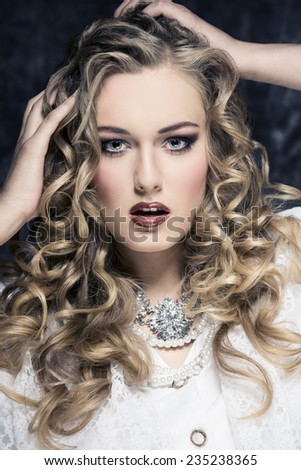 close-up fashion portrait of curly blonde girl with old fashion style, precious jewellery and white elegant clothes - stock photo