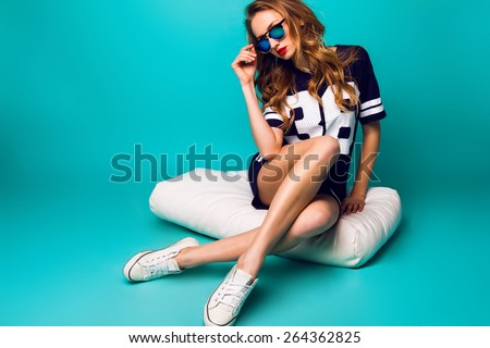 Close up fashion portrait of pretty sportive woman in stylish sunglasses, basketball t-short and white sneakers sitting on white pillow against bright aqua background . - stock photo