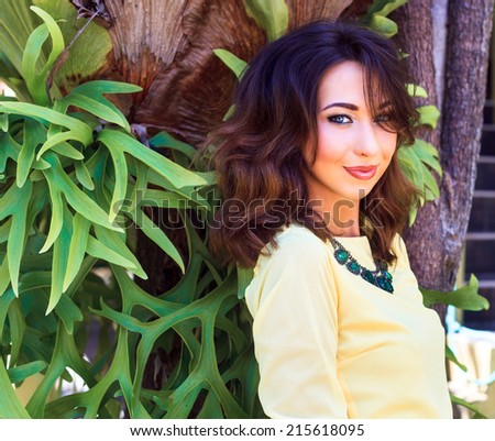 Close up fashion portrait of sensual beautiful brunette woman with bright make up, posing at exotic garden near beautiful fantastic tree, wearing blouse and big necklace. Have trendy hairstyle. - stock photo