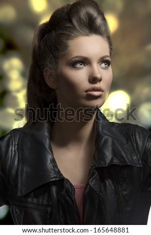 close-up fashion portrait of sensual young girl with brown rock hair-style wearing modern  clothes, black leather jacket - stock photo