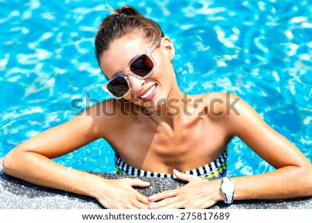 Close up fashion portrait of sexy tanned woman relaxed and swimming at pool. wearing bright bikini and sunglasses, smiling and looking on camera. - stock photo