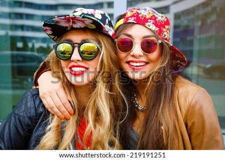 Close up fashion portrait of two pretty girls , wearing leather jackets swag hats and mirrored sunglasses, having blonde and brunette hairs and bright lips. Best friends positive portrait. - stock photo