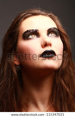 Close up fashion portrait of woman with black make up looking up - stock photo