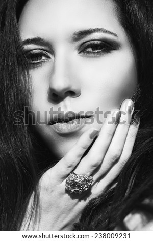 Close up fashion portrait of young beautiful woman brunette with long hair. Makeup color smoky eyes turquoise. Model shooting. Gold jewelry.Black and white photo