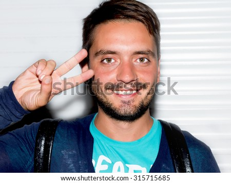 Close up fashion portrait of Young brunette man posing outdoors at night.Closeup of happy smiling guy looking at camera not isolated on white background.Portrait of smiling handsome brunet young man - stock photo