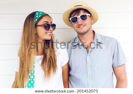 Close up fashion portrait of young couple posing near white wood floor in summer style clothes, retro sunglasses and hat. - stock photo
