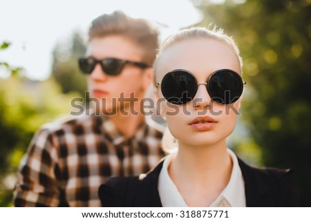 Close up fashion portrait of young couple posing on the city street in summer style clothes, retro sunglasses,fashionable couple in sunglasses,trendy outfits,autumn clothes,sunglasses fashion,black   - stock photo