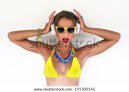 Close up fashion portrait of young pretty woman listening music in bright bikini at white background. - stock photo