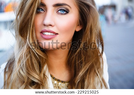 Close up fashion portrait of young sexy sensual seductive woman with perfect fluffy curled blonde hairs amazing smile and big blue eyes. - stock photo