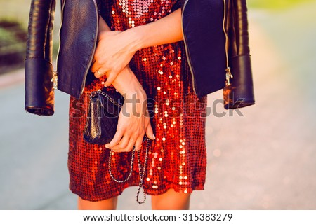Close-up fashion portrait of young stylish hipster girl posing at sunset,stylish woman's look,leather jacket,party handbag,toned colors,soft vintage colors,red dress,cocktail dress,fashion object  - stock photo