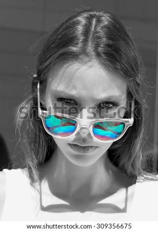 Close up fashion portrait of young woman. Close up fashion portrait of pretty hipster teenage girl with long brunette hairs, wearing stylish trendy mirrored blue sunglasses, Black and white concept - stock photo