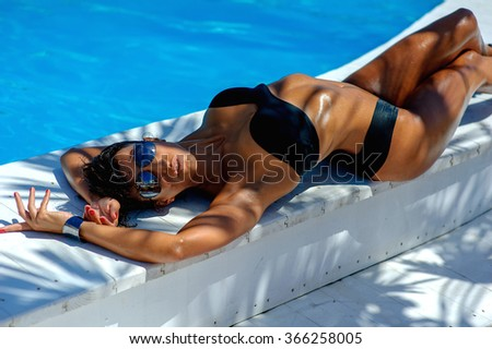 Close up fashion summer lifestyle portrait of sexy woman with tanned perfect body, relaxed laying near pool on her vacation,  wearing trendy sunglasses enjoying pool party on luxury villa. - stock photo