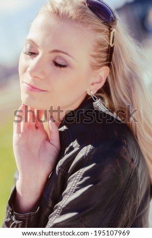 Close up, fashionable beautiful young blond wearing a leather jacket, warm sunny day - stock photo