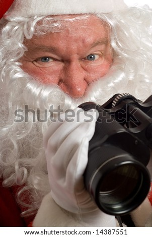 Close up Father Christmas with an odd look in his eye and binoculars - stock photo
