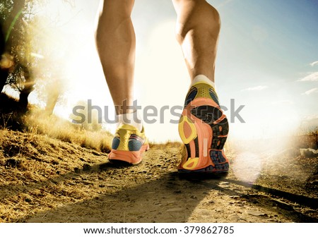close up feet with running shoes and strong athletic legs of sport man jogging in fitness training workout on off road trail track design in advertising poster style in sunset country background - stock photo