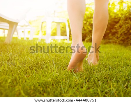 Close up female crossed legs walking on the grass in a park.